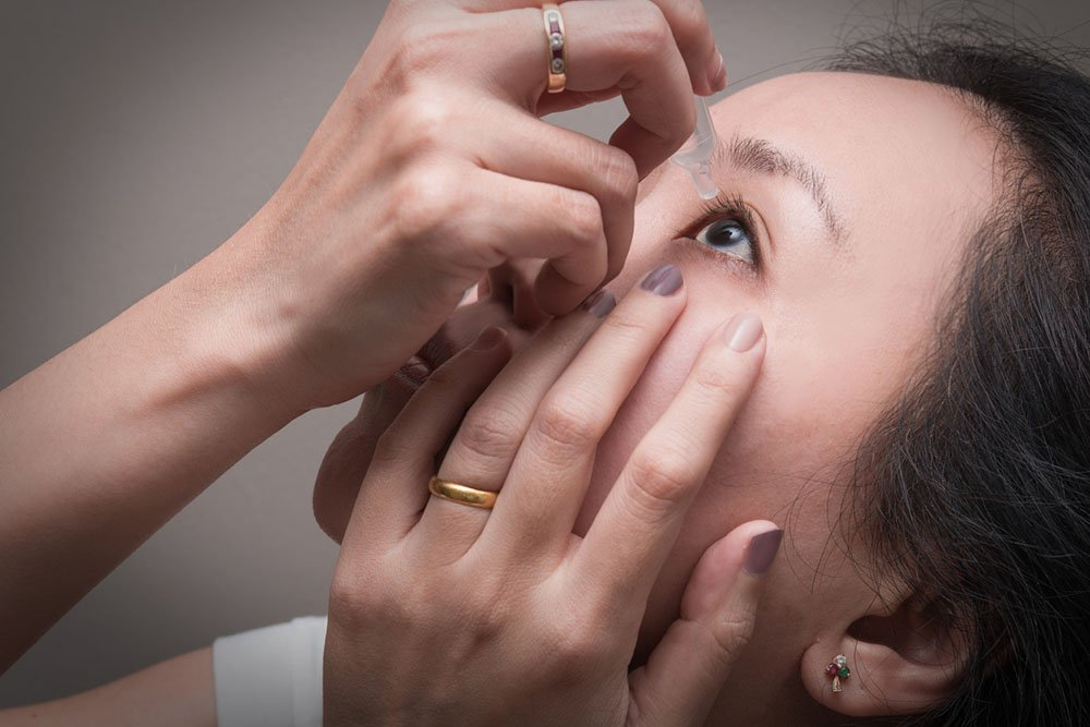 woman uses eye drops