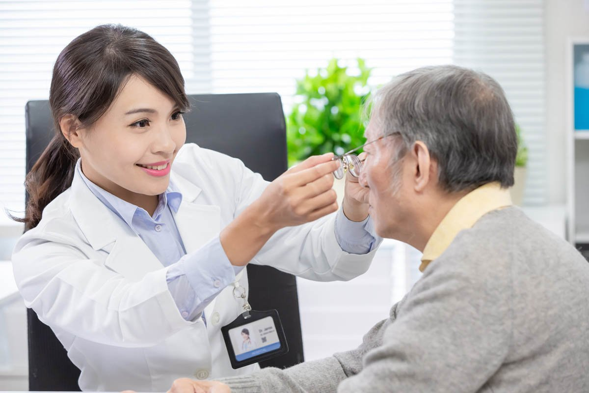 Ophthalmologist see an elderly patient and helping him to wear glasses
